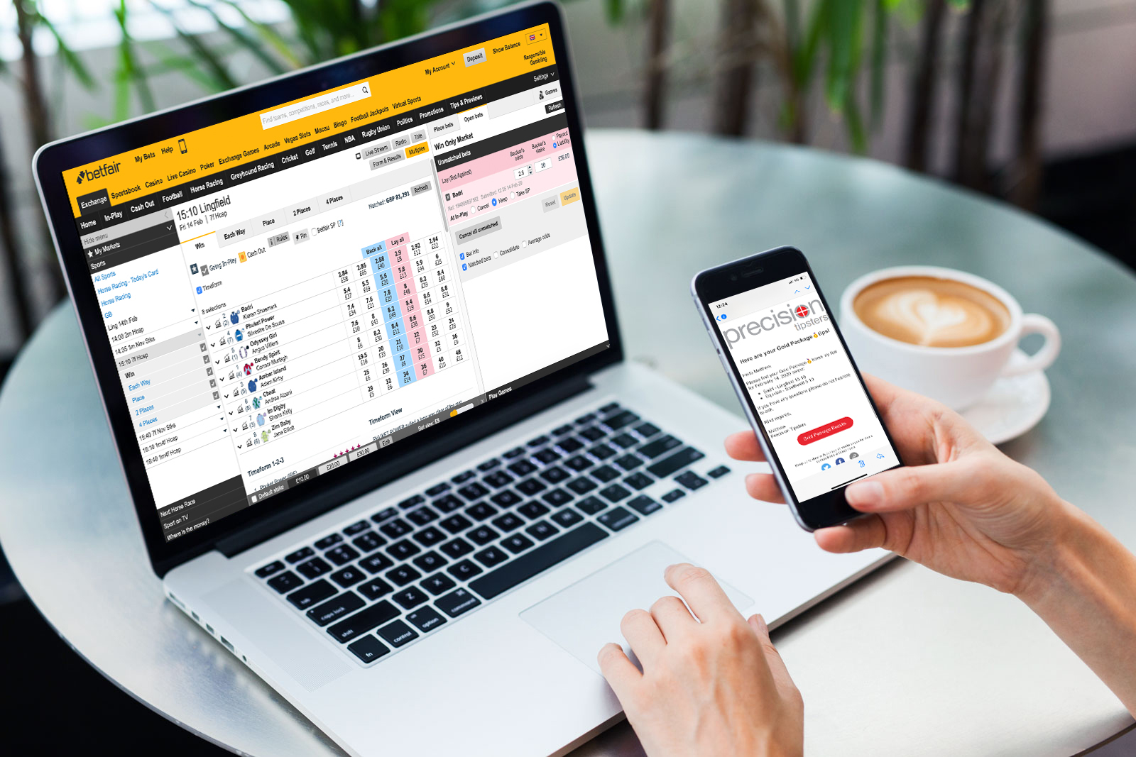 Laptop and iphone placing bet on betfair with emailed tips