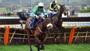 Photo of horse hurdling over fence